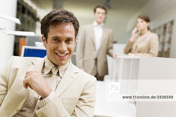 Porträt von lächelnd Geschäftsmann an Schreibtisch im Büro sitzen
