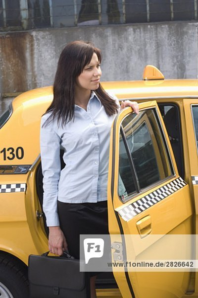 young businesswoman leaving yellow taxi