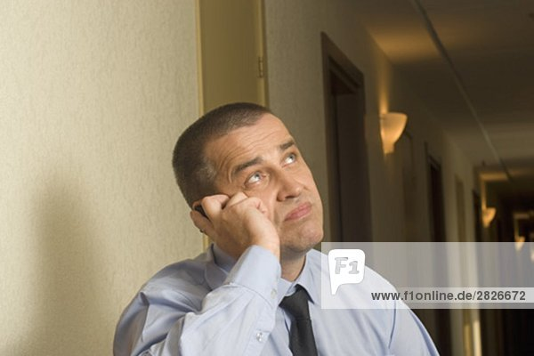 Porträt von Reifen Geschäftsmann in Hotel Korridor sprechen auf Handy