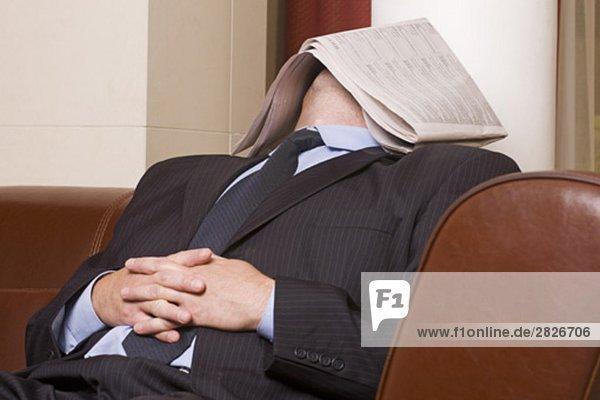 Kaufmann dösen in Hotel-Lobby mit Zeitung über sein Gesicht