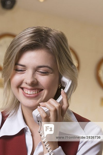 headshot of young hotel receptionist talking on telephone