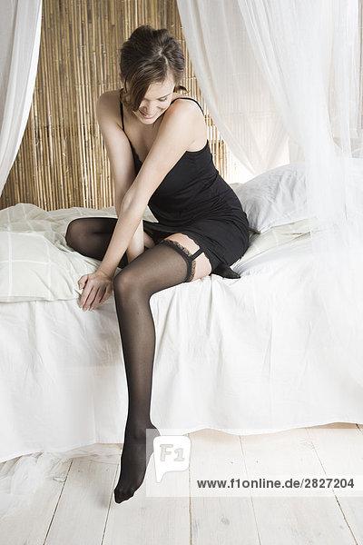 Schöne Frau sitzen auf dem Bett