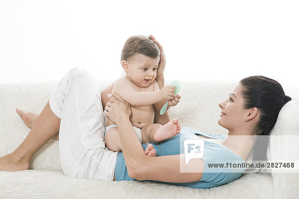 Mother playing with baby on sofa