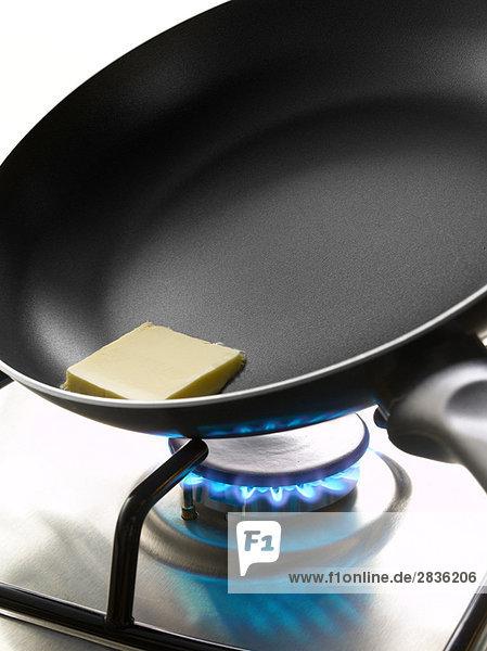 Stück Butter in einer Pfanne auf einem Gaskocher