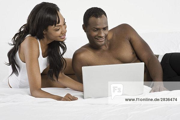 Mittelaltes Pärchen das Laptop in Schlafzimmer benutzt