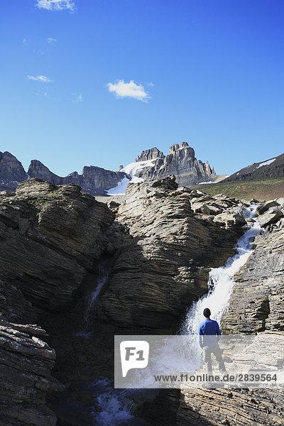Wanderer Blick auf ein Wasserfall am Dolomit Creek mit Dolomit Peak im Hintergrund  Banff-Nationalpark  Alberta  Kanada.