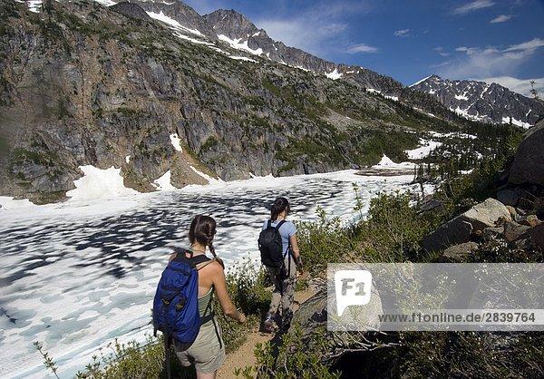 Zwei Frauen Wanderer Wandern neben frozen Lake Kokanee  Kokanee Gletscher Provincial Park  Kootenays  British Columbia  Kanada.