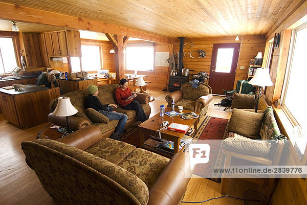 Two middle-aged woman enjoying an alpine cabin  Valkyr Adventures Lodge  Selkirk Mountains  British Columbia  Canada.
