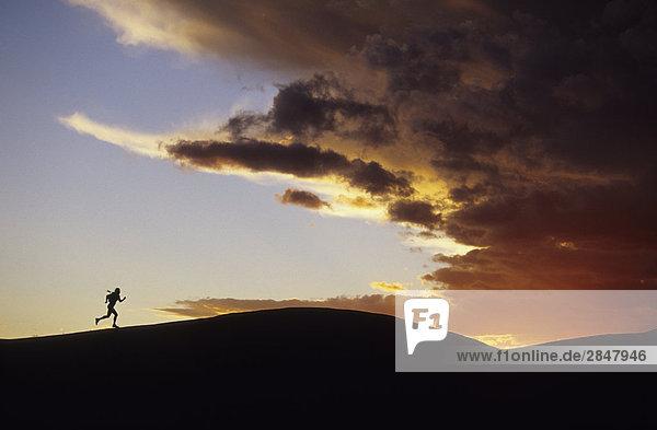 Eine Silhouette ein Läufer auf dem Hintergrund der eine brillante Sonnenuntergang  Moab  Utah  USA.