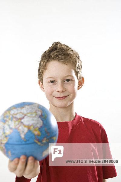 Junge hält Globe und lächelnd