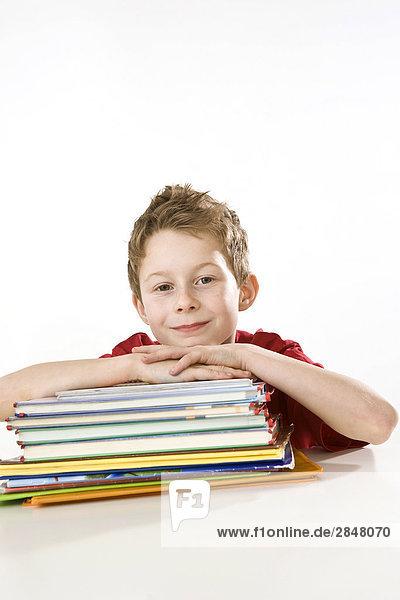 Junge stützte sich auf Bücher und lächelnd