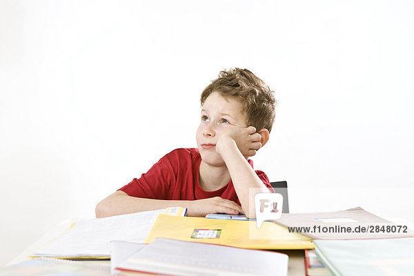Junge stützte sich auf Bücher und denken