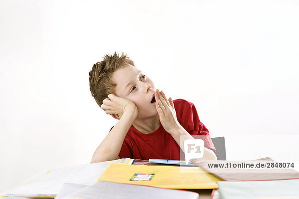 Junge stützte sich auf Bücher und Gähnen