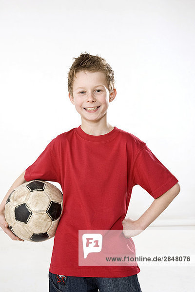 Junge hält Soccer Ball und lächelnd