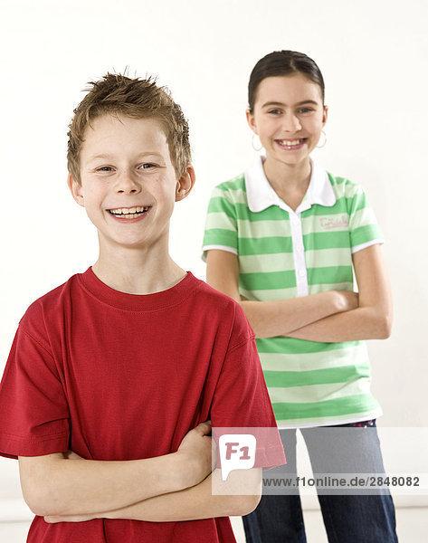 Junge und seine Schwester stehen mit ihren Armen überquerte und lächelnd
