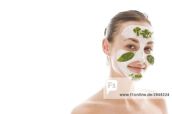 junge Frau mit herbal Gesichtsmaske