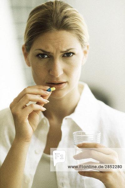 Woman holding pill  frowning at camera