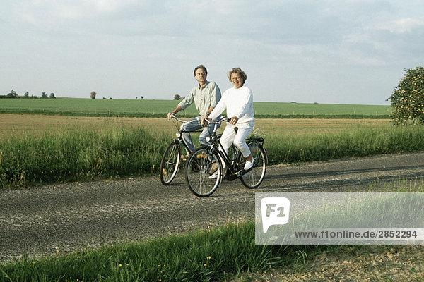 Paar Fahrräder durch die Landschaft  lächelnd vor der Kamera