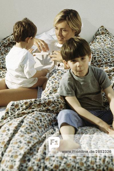 Mutter und zwei Kinder  die im Bett faulenzen.