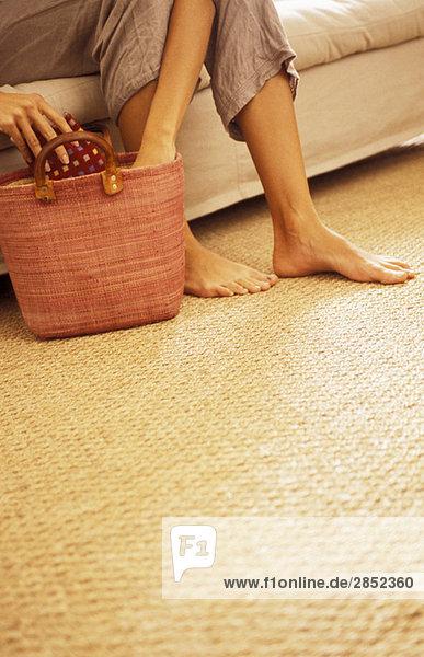 Frau greift in die Tasche auf dem Boden  niedrige Sektion