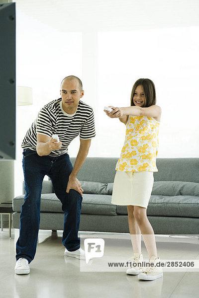 Vater und Tochter spielen Videospiel mit drahtlosen Controllern