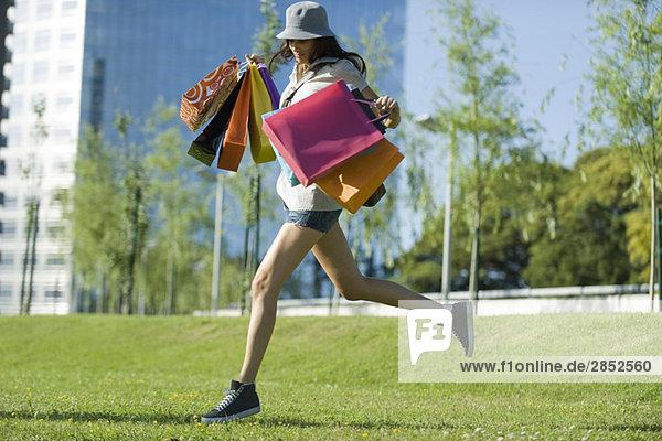 Junge Frau läuft durch den Park und trägt mehrere Einkaufstaschen.