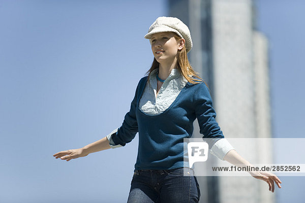 Junge Frau mit trendigem Hut  im Freien stehend und mit ausgestreckten Armen.