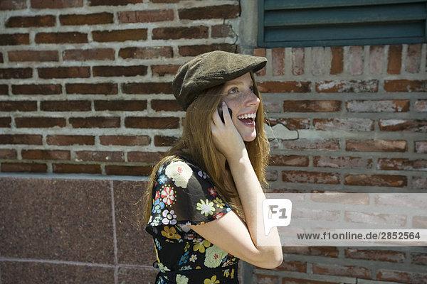 Junge Frau mit trendigem Hut und Handygespräch