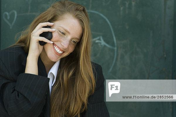 Junge Frau mit erdbeerblonden Haaren spricht am Handy