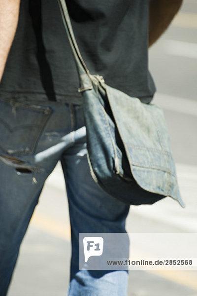 Person mit Denim-Umhängetasche  von hinten gesehen  beschnitten