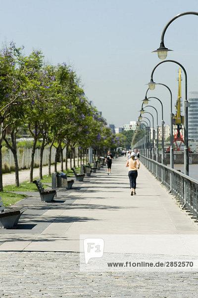 Menschen joggen auf dem Bürgersteig im Park