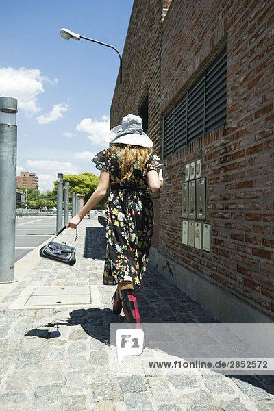 Junge Frau in trendiger Kleidung auf dem Bürgersteig  Rückansicht