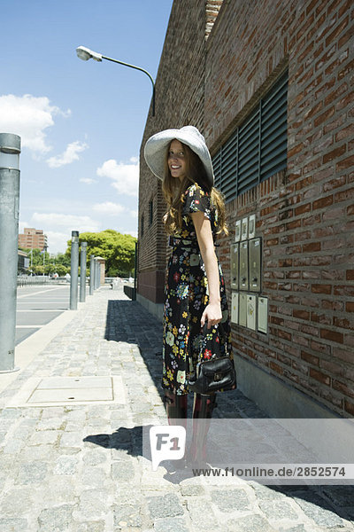 Trendige junge Frau auf dem Bürgersteig  lächelnd über die Schulter vor der Kamera
