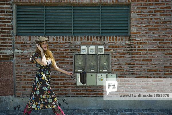 Junge Frau in trendiger Kleidung  die auf dem Bürgersteig läuft und mit dem Handy plaudert.