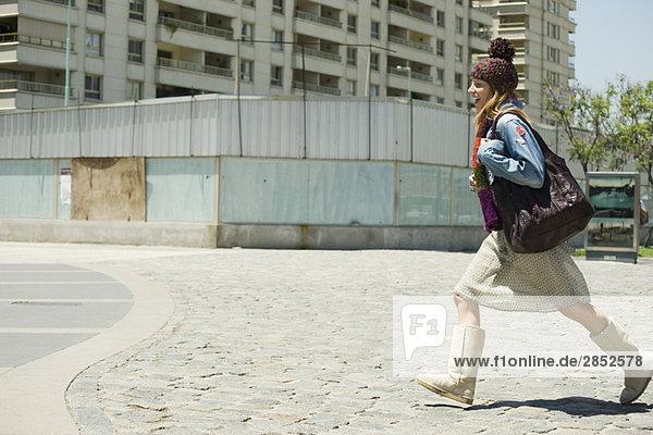 Trendige junge Frau auf dem Bürgersteig  Seitenansicht