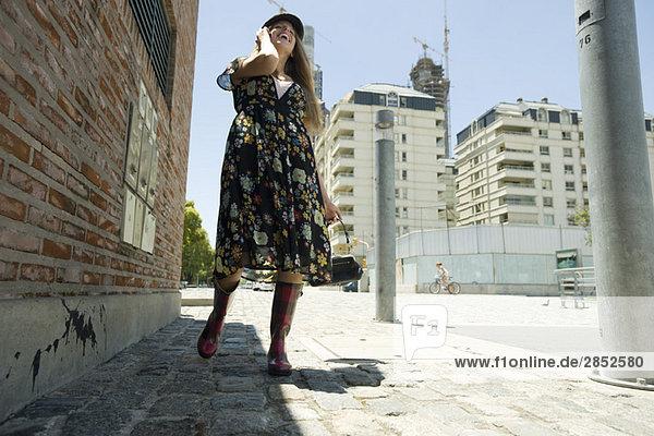 Junge Frau  die auf dem Bürgersteig geht und mit dem Handy telefoniert.