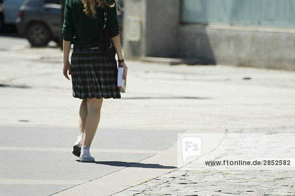 Junge Frau auf dem Bürgersteig  Tragebuch  Rückansicht
