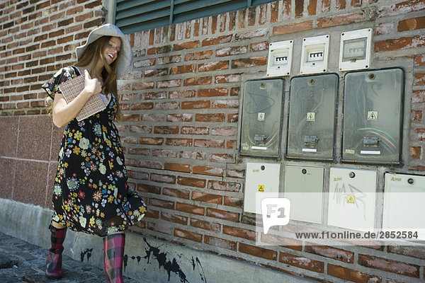 Junge Frau in trendiger Kleidung  die auf dem Bürgersteig läuft