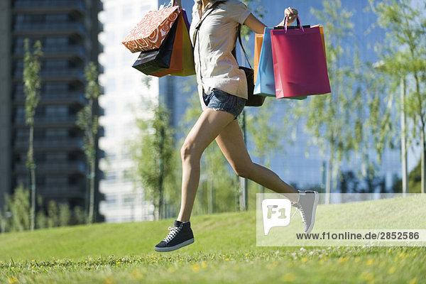 Junge Frau läuft im Park und trägt Einkaufstaschen.