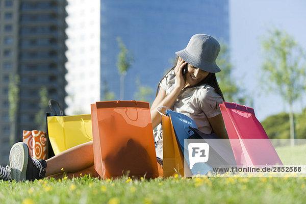 Junge Frau auf dem Boden sitzend  umgeben von Einkaufstaschen  am Handy sprechend
