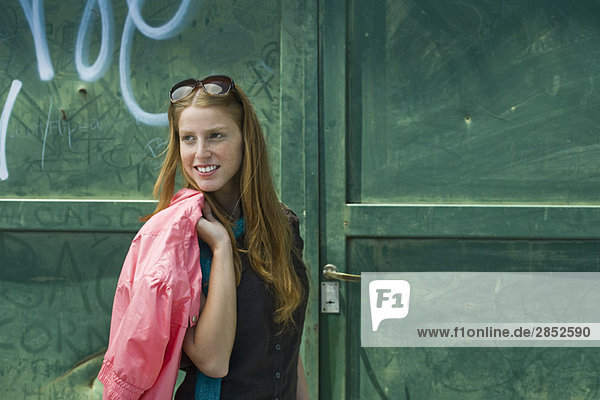 Modische junge Frau vor graffitierter Tür stehend  Jacke über die Schulter geschlungen