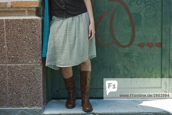Junge Frau in trendiger Kleidung an der Wand lehnend  niedriger Schnitt