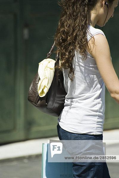Lässig gekleidete Frau mit Geldbörse und Dokumenten  Seitenansicht
