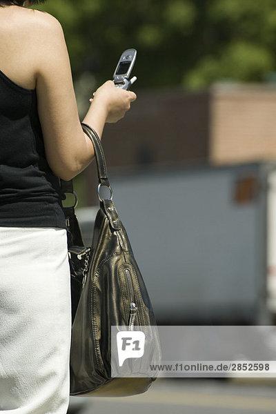 Frau hält Geldbörse  schaut auf Handy  abgeschnittene Rückansicht