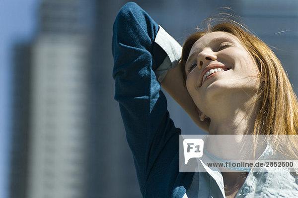 Junge Frau im Freien  lächelnd mit einer Hand hinter dem Kopf und geschlossenen Augen.
