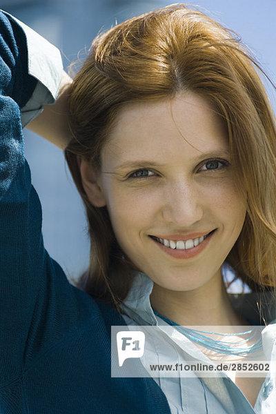 Junge Frau lächelt vor der Kamera  eine Hand hinter dem Kopf  Portrait
