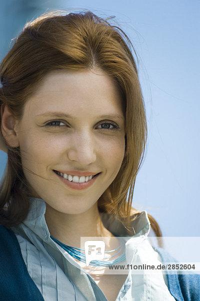 Rothaarige Frau lächelt vor der Kamera  Portrait