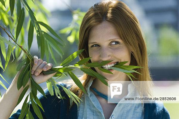 Junge Frau mit Zweig in den Zähnen  Portrait