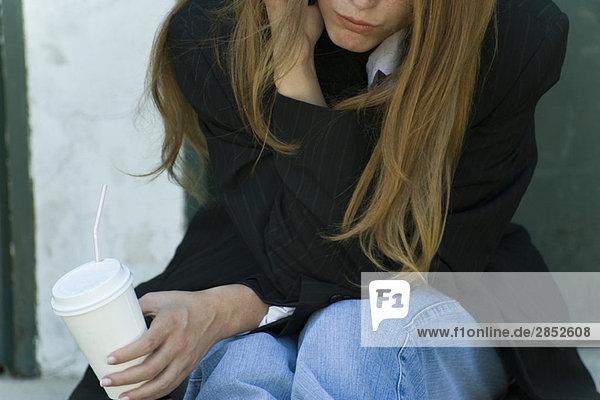 Junge Frau  die sich auf den Ellenbogen stützt  Tasse haltend  Ausschnittansicht