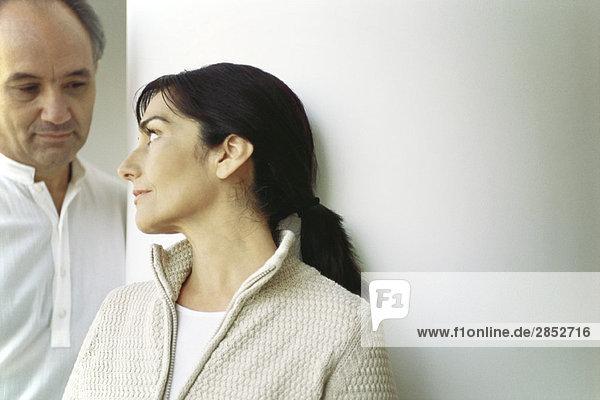 Reife Frau  die sich gegen die Wand lehnt und den Ehemann ansieht.